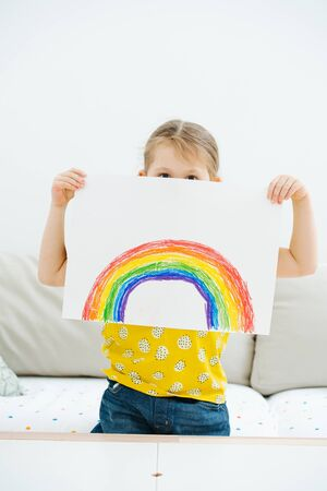 Little girl showing a rainbow she just painted. It partially covering her face.