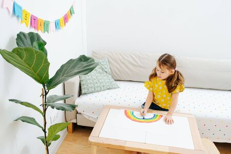 Little girl drawing rainbow on a sheet of paper on a coffee table in a living room. Stay home flag garland hanging on the wall. Banque d'images