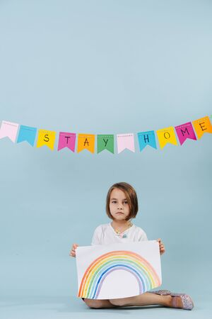 Tired little girl showing a rainbow she just painted. Sitting on the floor. Over blue background. Stay home garland hanging across. Banque d'images