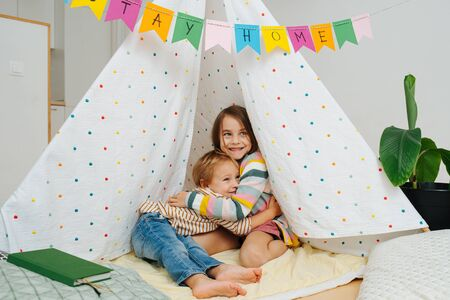 Little siblings sitting on a blanket in a hut, made with sticks and bedsheets. They are hugging and looking at a camera.