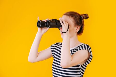 Girl in search with binoculars in hand, studio portrait on yellow background