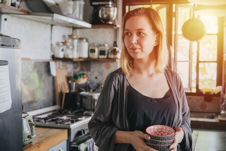 Portrait of a mature woman in an old narrow cluttered kitchen with orange setting sun in a window.