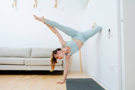 Body flexibility is a beautiful pose. The girl in good training arranged a home workout on acrobatics, leaning on the wall with her foot and standing on one hand