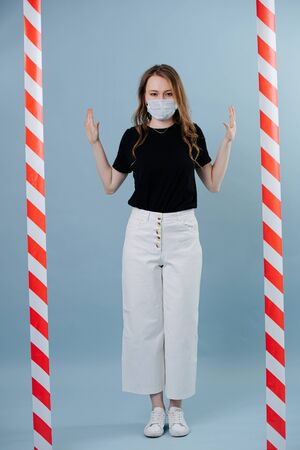 You can't go any further. Image of girl full length in protective mask, she stopped in front of the forbidden passage tape Stock Photo