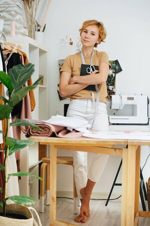 Portrait of a clothing designer standing in the studio with scissors, a notepad and measuring tape