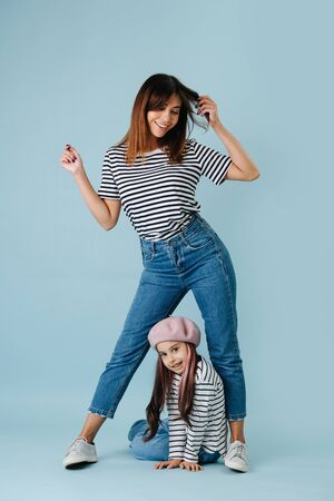 Two fashion lovers, mom and daughter wearing same clothes over blue background. They have jeans and black and white striped shirt on them. Mom in a flattering pose, looking down at her daughter.