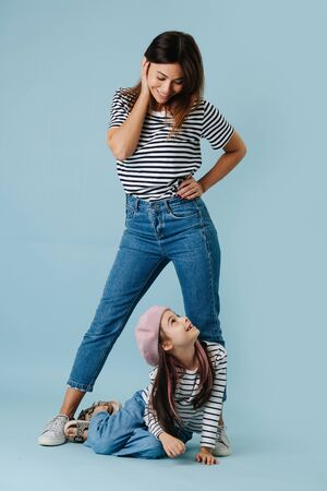 Two fashion lovers, mom and daughter wearing same clothes. They have jeans and black and white striped shirt on them. Mom in a flattering pose, looking down at her daughter, she looks back.