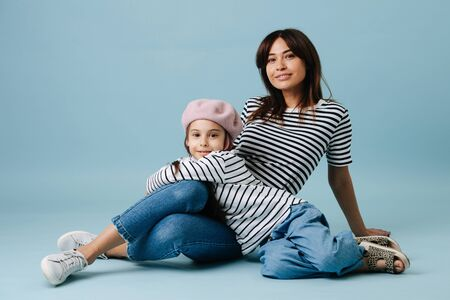 Two fashion lovers, mom and daughter wearing same clothes. They have jeans and black and white striped shirt on them. Mom sitting on the floor and leaning on the floor. Dau leaning on her.