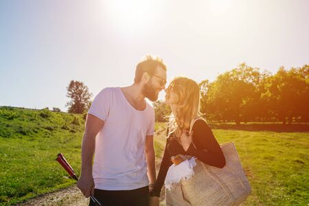 Two people in love kissing on the road to picnic. On a beautiful sunny day in a green countryside.