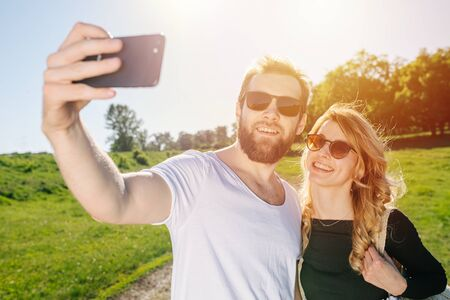 Happy smiling couple taking selfie on a sunny day outdoors, in rural area. Over fields, trees and sky. Wearing sunglasses.