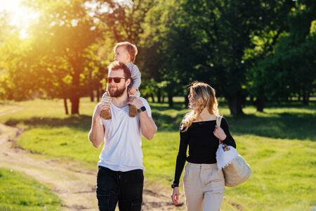 Happy idyllic family walking in countryside during beautiful sunny day outside. Babby rides on his dad's shouders, he and his wife can't stop smiling.