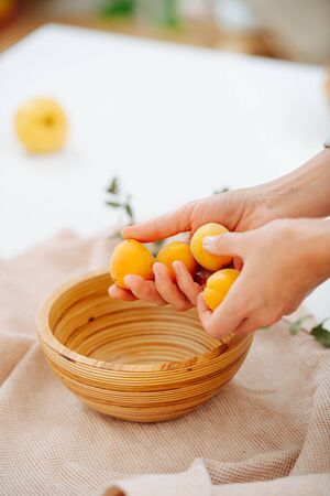 Woman hands placing fresh ripe apricots in a handmade wooden bowl of good quality, standing on a cloth covered pedestal.