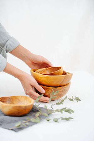 Woman hands placing stack of handmade wooden bowls on a white surface next to one standing on a napkin. Dried brach complete a composition. Foto de archivo