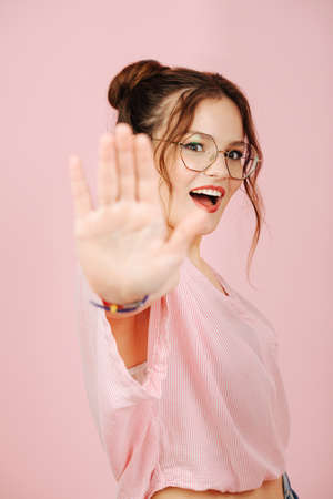 Emotional girl in glasses with two buns making stop gesture, blocking camera
