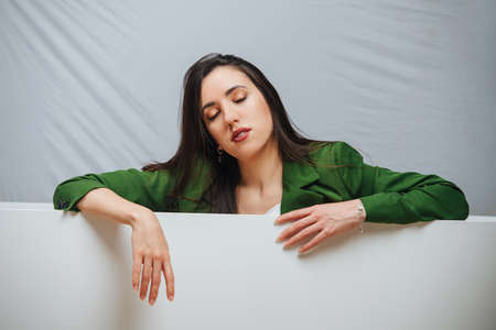 Tired young woman with sleepy face leaning on an edge of an empty bathtub. Her eyes closed. She's wearing green jacket.