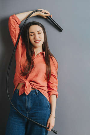 Portrait of a happy stunning beautiful woman pretending to shower with a sprinkler in a tube shape. Her eyes closed. She wears bright orange belly-tied dress shirt and jeans.