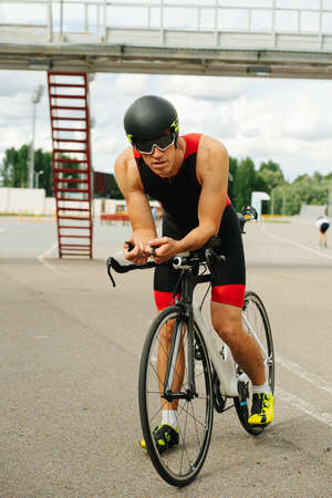 Male athlete sitting on a pro slim bike geared up with streamlined helmet. Side view. He's wearing one piece cycling jersey. Looking at camera through sunglasses.