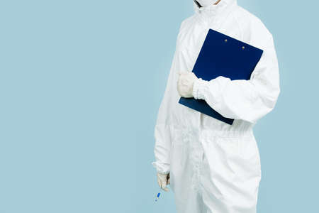Fully geared up doctor in a white costume covering all skin and gloves holding plastic folder. Cropped, body and hips, no head.