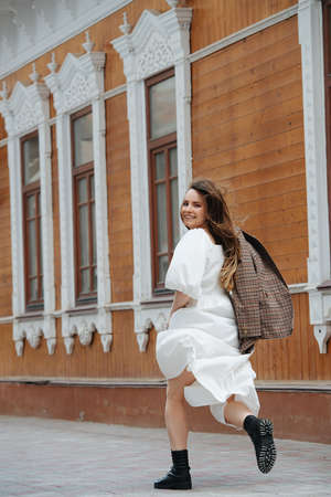 Happy young woman running up paved street in a white fluffy dress and heavy boots. Along big wooden building with tall windows. Carrying checkered jacket in hand. Looking behind at the camera.