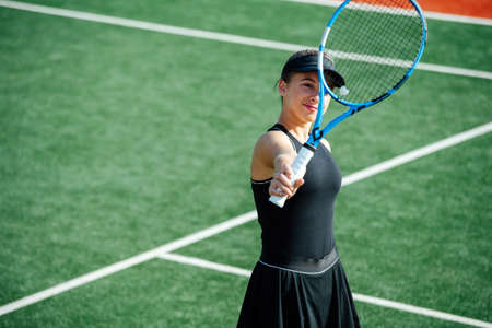 Teenage girl in a sportive outfit standing in the middle of a brand new tennis court on a sunny day. Stockfoto