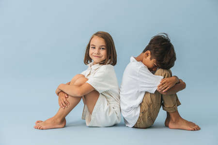 Little boy and girl of roughly the same age sitting on the floor, leaning their backs on each other. Over blue background.