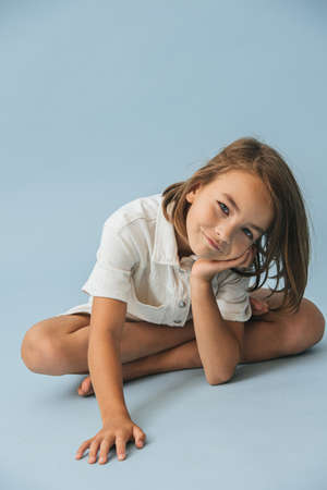 Smiling ten year old little girl in a white thick romper suit sitting on the floor, leaning on her hand, playing cute. Over blue background.