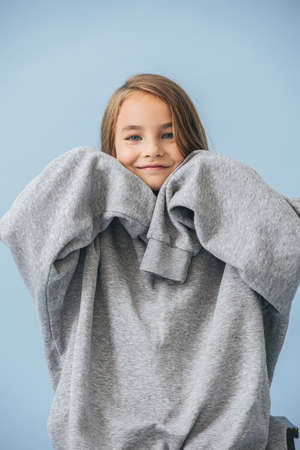 Cute smiling little girl in a huge oversized grey longsleeve over blue 스톡 콘텐츠 - 154748710