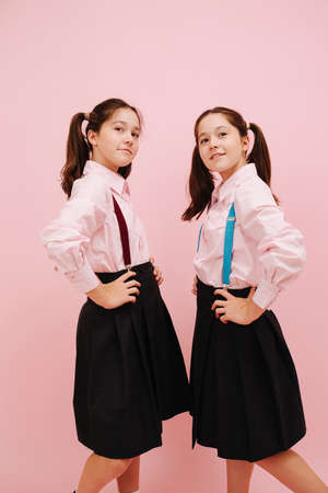 Beautiful little twin schoolgirls with twintails happily posing in uniform. Low angle. Over pink background, studio shot. They have braces of different color on their skirts. Hands on hips