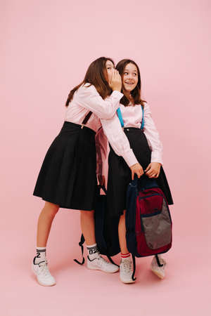 Beautiful little twin schoolgirls happily posing with their backpacks, looking at the camera. Low angle. Over pink background, studio shot. One of them wispers in a second one's ear.
