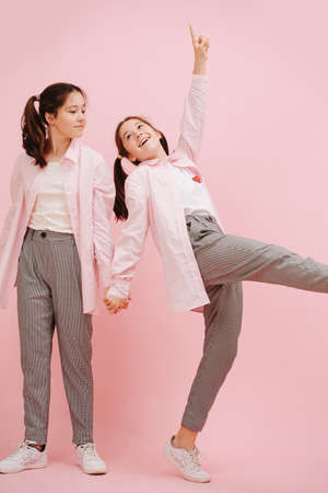 Beautiful little twin sisters happily playing. Over pink background, studio shot. Holding hands. One is artistically walking, looking at the other. Wearing pink dress shirts and checkered pants.