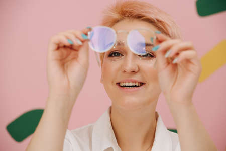 Happy young woman looking at glasses she's holding. She has short dyed blond hair and round glasses and stars eye makeup. Over pink background. Mouth open in a smile.