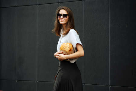 Happy mature business woman in sunglasses on the street, carrying crispy bread under her arm. She's wearing corporate clothing.