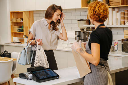 Young woman looking at available goods, female baker standing behing cash register, looking at client.