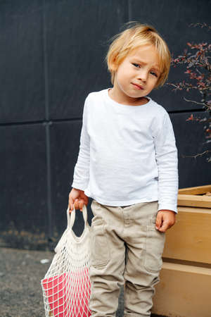 Little boy with blond hair holding net bag with toy bucket, outdoors on the street. Over back panels, next to planter box.