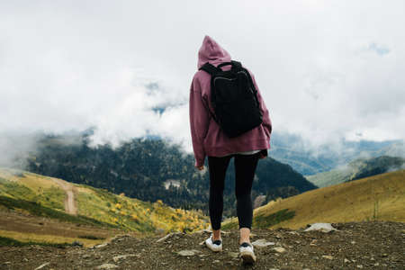 Young woman in mountains covered with short grass and trees, low clouds hanging around her. She's wearing hoodie, yoga pants and backpack, Enjoying the view.