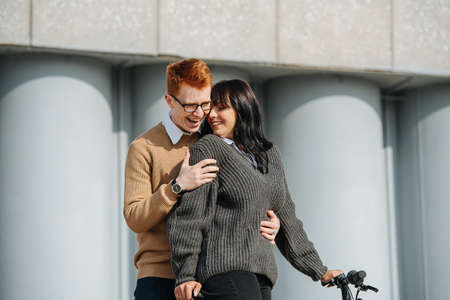 Perfect couple, young man hugging girlfriend on ebike, she snuggles back