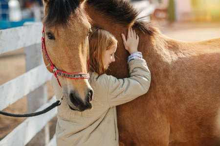 Friendship of a little ginger girl and her horse. Touching and leaning to each other.