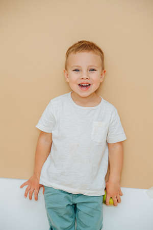 Portrait of a cheerful 5 year old boy over brown background. He has cute smile. Holding apple in hand.