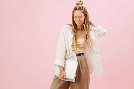 Stunning eccentric young woman with stylish blond afro braids over pink background. She's posing for a photo, one hand on a back of her head, holding notebook in a second hand.