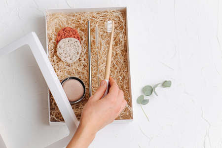 Female hand picking wooden toothbrush form box with multi-use eco-friendly items. It also contains steel straw and woven makeup remover discs on a filling paper.