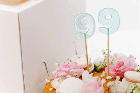 Close up image of a honey cake with flowers and macarons next to white box. number 99 on sticks sticked in the cake. Cropped. top part only.