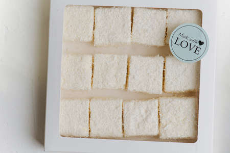 White turkish delight under coconut shavings in a windowed box with a made with love sticker. Top view.