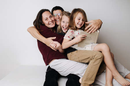 Happy family sitting together on table. Dad grabed wife and kids in his embrace
