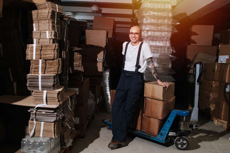 Smiling male warehouse worker leaning on stack of carton boxes on pallet jack