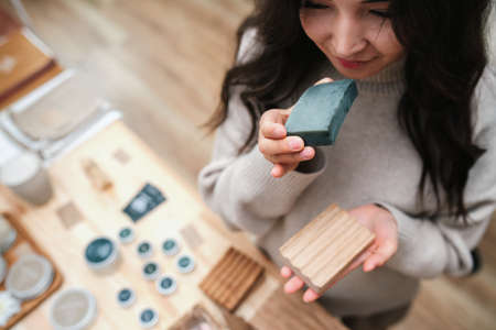 Blissful woman holds eco soap and wooden soap dish. Smelling soap. Overhead view