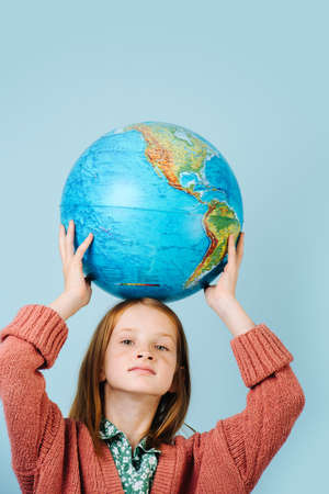 Red-haired girl with a globe in her hands