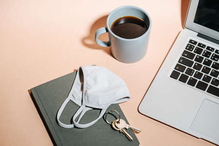 Laptop, coffee, medical mask, notebook and keys on a peach colored surface
