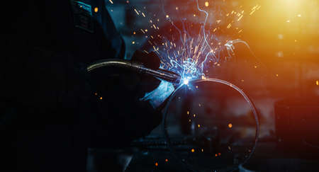 Close-up of gas metal arc welding, blue gas glow and yellow flying sparks