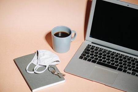 Work kit in coronavirus reality. Laptop, coffee, medical mask, notebook and keys