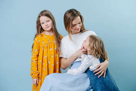 Mom and two daughters socialize together on a blue background
